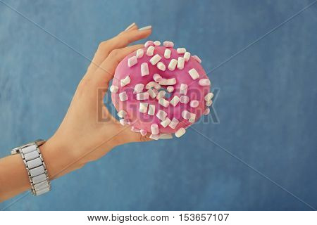 Female hand holding tasty donut on color background