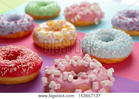 Tasty donuts with sprinkles on colorful background