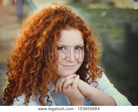 Redheaded beautiful girl on a background of nature