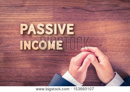Passive income concept. Businessman hands in passive gesture and wooden text passive income.