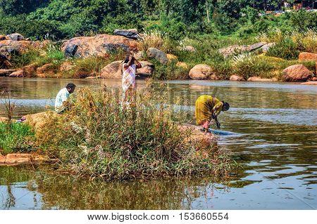 Hampi India - November 20, 2012: Unidentified Indian women wash their clothes on a rock in the Tungabhadra River in Hampi Karnataka India