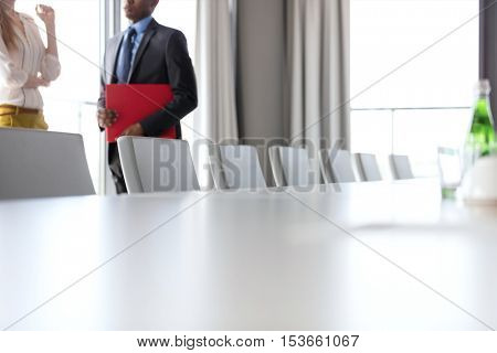 Midsection of businessman and businesswoman standing by conference table in office