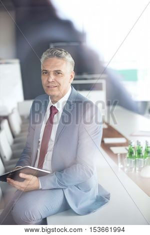 Portrait of confident mature businessman holding digital tablet while sitting on conference table