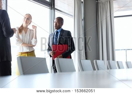 Business people having discussion while standing by conference table in office