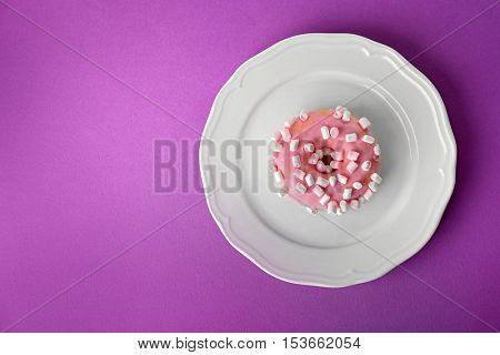 Plate with tasty donut on color background