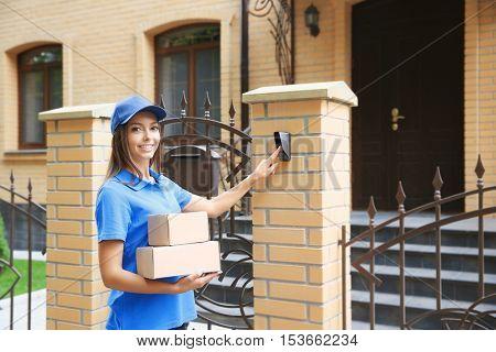 Female courier in uniform ringing in doorbell