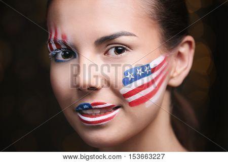 Girl with USA makeup on bokeh lights background