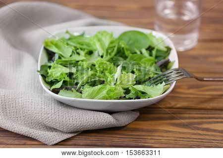 Fresh delicious salad on wooden background, closeup