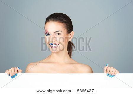Girl with USA makeup and blank paper on grey background