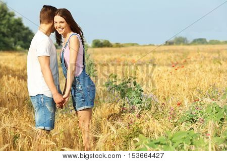 Young couple holding hands on beautiful field