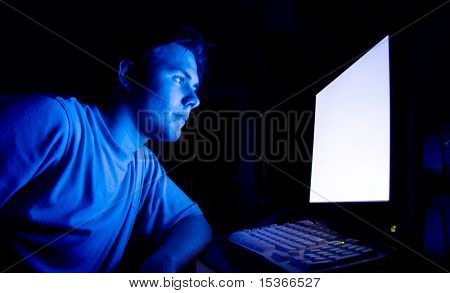 Man in front of computer. Dark night room.