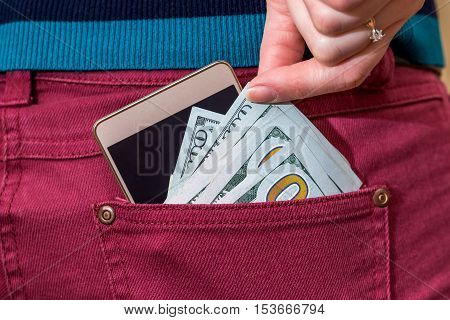 Female hand pick 100 dollar banknotes and mobile from jeans back pocket
