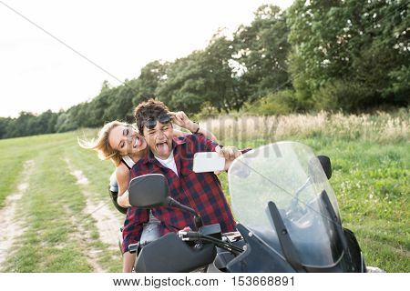 Beautiful young couple in love enjoying a quad bike ride in countryside. Couple driving off-road with ATV. Taking selfie with smart phone, grimacing.