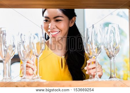 Asian woman in furniture store choosing glasses