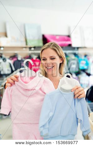 Beautiful pregnant woman shopping clothes for her baby, not knowing whether to buy blue for boy or pink for girl