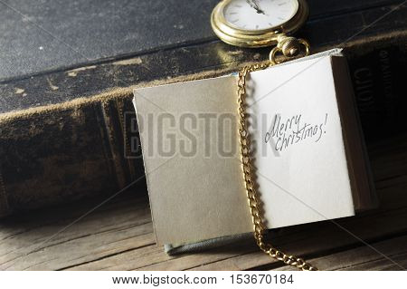 Merry Christmas - inscription, gold pocket watch and old vintage book.