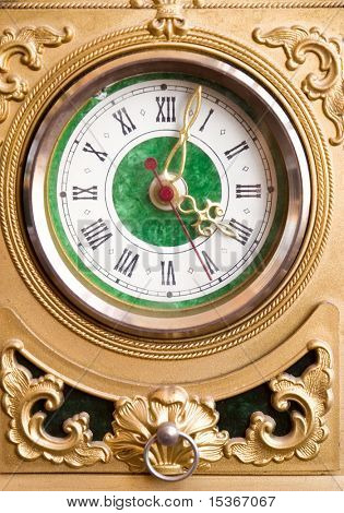 Antique goldish clock. Front view.