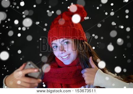Closeup happy teen girl in winter knit hat and warm scarf with smart phone gesturing thumb up, over dark grey background with snow flakes