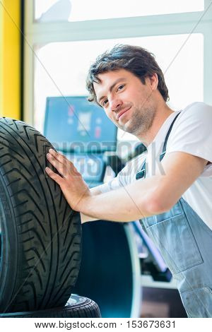 Auto mechanic changing tire in car workshop