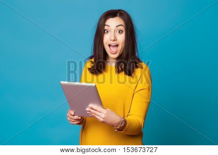 Surprised young woman wearing yellow clothes using tablet pc isolated on vivid blue background