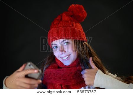 Closeup happy teen girl in winter knit hat and warm scarf with smart phone gesturing thumb up, over dark grey background