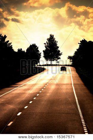 Eine Straße mit einsamen Auto. Rote Sonnenuntergang Licht und hohen Kontrast.