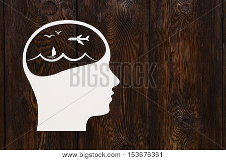 Paper head with sea waves and plane inside, copy space. Travel concept. Abstract conceptual image. Dark wooden background