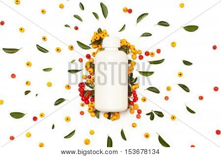 White plastic cosmetic bottle with green fresh leaves and yellow and red Pyracantha berries isolated on white background. Flat lay top view.