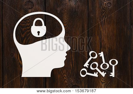 Paper head with padlock, stack of keys near. Concept. Abstract conceptual image with copyspace. Dark wooden background