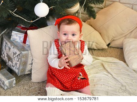 Cute little girl sitting under the Christmas tree and holding a gift in her hands