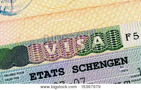 Schengen visa in passport closeup.