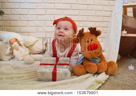 Cute little girl and toy deer under the Christmas tree. Baby holding a gift in her hands and smiling