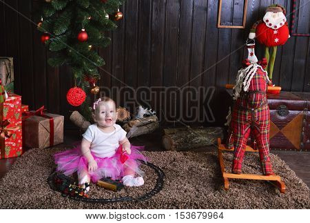 Cute little girl sitting under the Christmas tree. Child playing with a toy train