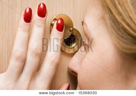 Woman looking into spy hole closeup.