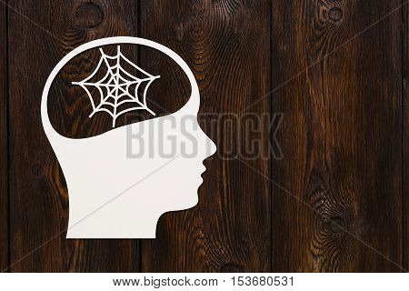Paper head with spider's web inside. Knowledge concept. Abstract conceptual image with copyspace. Dark wooden background