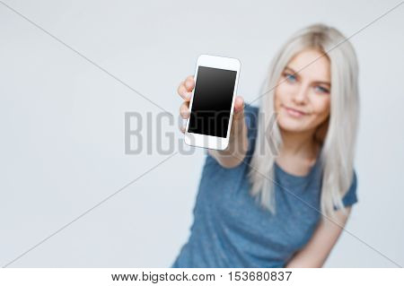 Teenage girl showing a blank smartphone screen. Focus on smartphone. Cute young blond student in background