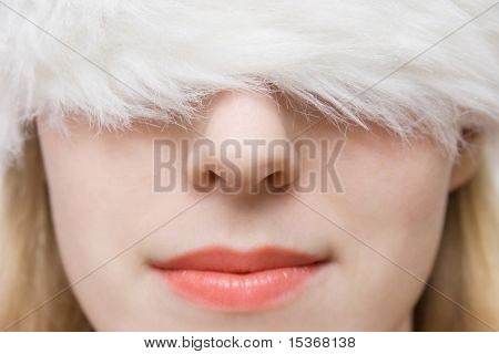 Young woman in big fluffy cap. Portrait closeup.