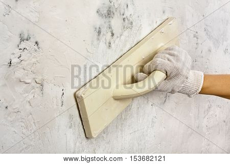 hand with trowel plastering and smoothing concrete wall during repair
