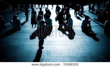 Walking people silhouettes blue tint. High contrast and deep shadows.