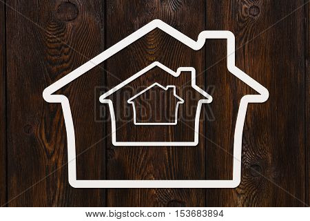 Paper house with small copy inside. Infinity concept. Abstract conceptual image. Dark wooden background