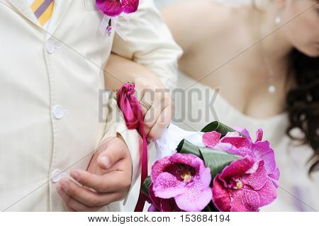 Bride and grooms holding their hands on summer day