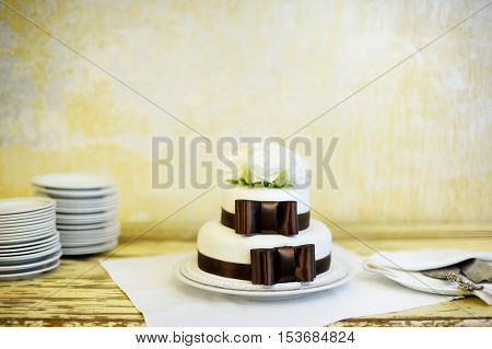 Delicious white and brown wedding cake on a table