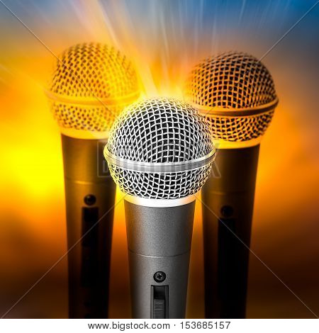 Golden light on triple silver microphone on blured background