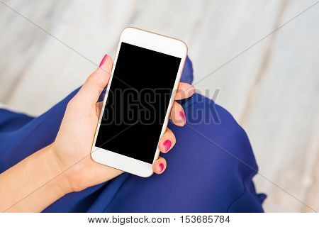 Woman holding smartphone with black screen in her hands