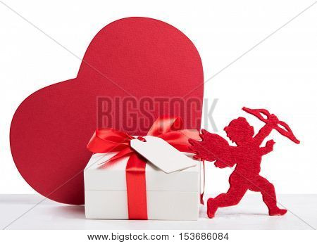 Close up of small gift box for valentine day isolated on white background. Valentine present with greeting card and red cardboard heart shape. Love valentine day with cupid and romatic gift box.