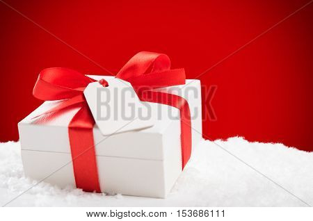 Close up of christmas gift box on snow with white greeting card. White xmas present with red ribbon on red background.
