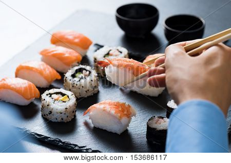 Man holding chopstick and eating sushi at reastaurant. Close up of businessman hands dining at japanese restauranti. Close up hand of man holding wooden chopstick with sushi for lunch break.