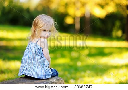 Angry little girl portrait outdoors on summer day