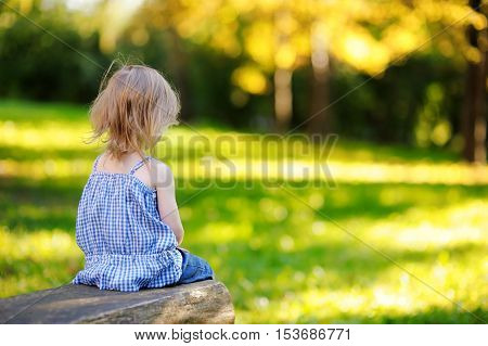 Angry little girl sitting outdoors on summer day