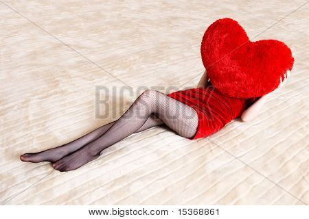 Young sexy woman on big counterpane holding red heart pillow.
